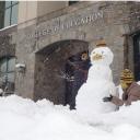 Kids build snowmen in front of RCOE